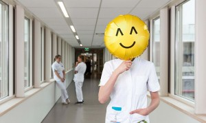 verpleegkundige met een smiley ballon voor haar hoofd